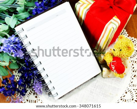 teddy bear sitting with a red heart and christmas gift with note book paper background - stock photo