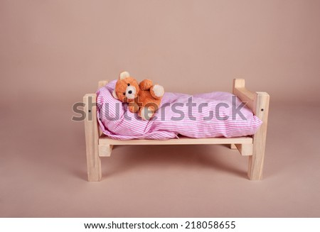 Teddy bear sleeping on baby cot on beige background in studio - stock photo