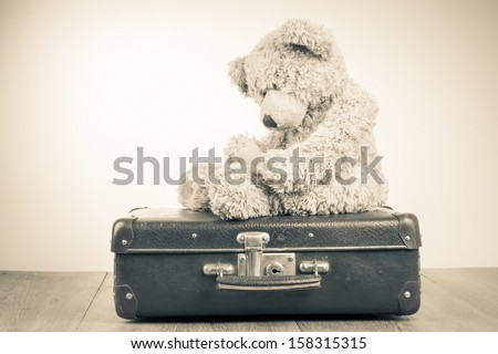 Teddy Bear toy alone on suit case retro sepia photo - stock photo