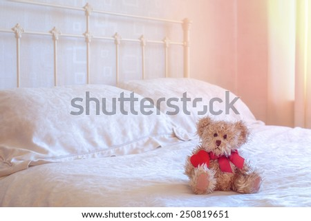 Teddy bear toy sitting on the bed holding a red heart - stock photo