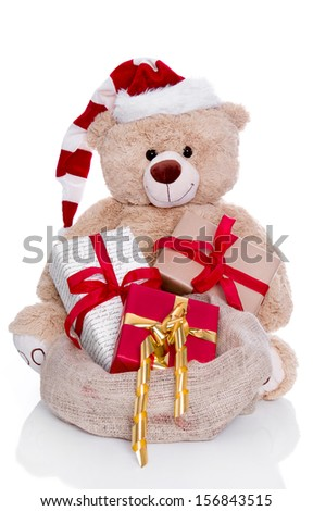 Teddy bear wearing Christmas hat with gifts isolated on white background