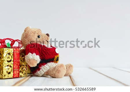 Teddy Bear wearing Santa Claus knitted sweaters with gift box. Concept about season greetings. Merry Christmas Celebration