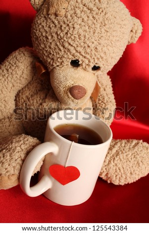 Teddy bear with a big white cup of tea and a red heart
