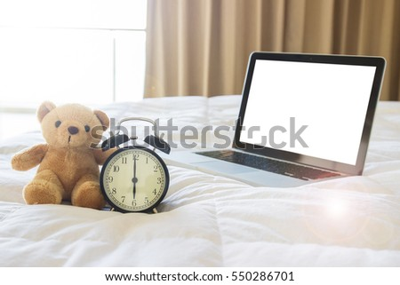 Teddy bear with alarm clock and computer laptop white isolated background on comfort bed with lens flare