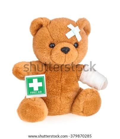 Teddy bear with bandage isolated on white - stock photo