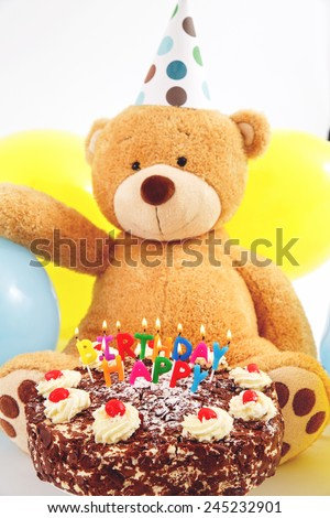 Teddy bear with birthday cap, balloons and cake with candles. Birthday greeting card. Happy birthday cake with burning candles.