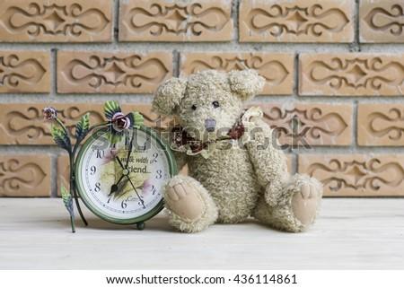 Teddy bear with clock on brick wall background. - stock photo