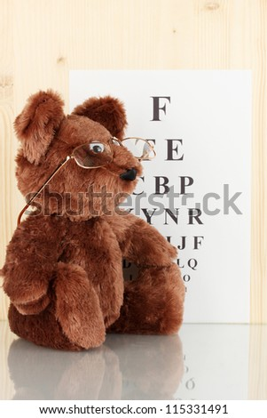 Teddy bear with glasses on eyesight test chart background close-up - stock photo