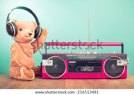 Teddy Bear with headphones, retro radio recorder front mint green background - stock photo