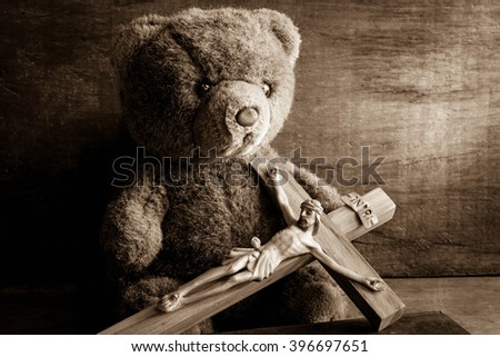 Teddy bear with jesus and the cross,Faith belief and hope concept - stock photo