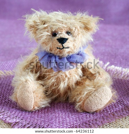 Teddy bear with neck ruffle sitting on purple and natural hessian - stock photo