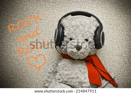 Teddy Bear with orange scarf listening to music on headphones. Lover of rock and roll - stock photo