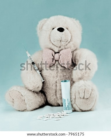 teddy bear with pills and a syringe - stock photo