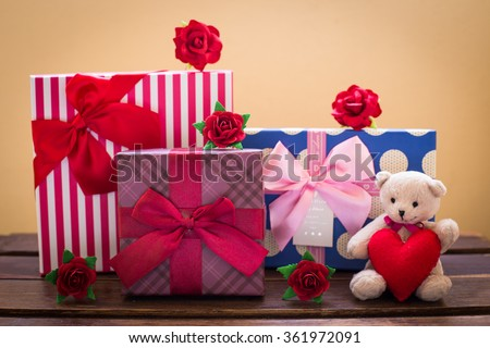 Teddy bear with pink heart decoration on rose and present gift on blue background/ Valentines day background. - stock photo
