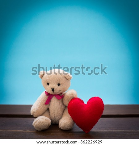 Teddy bear with pink heart decoration on wooden table over wall blue background, Valentine day concept. - stock photo
