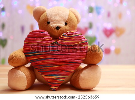 Teddy Bear with red heart on festive background - stock photo