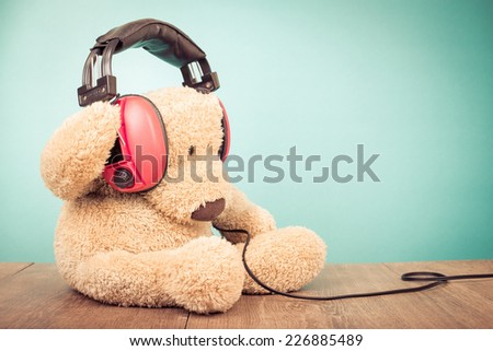 Teddy Bear with retro red headphones front mint green background - stock photo