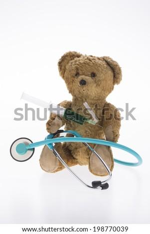 teddy bear with stethoscope and syringe - stock photo