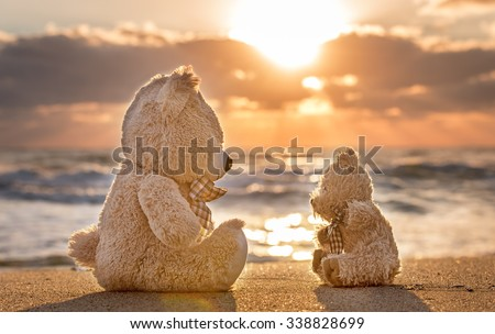 Teddy bears sitting on the beautiful beach with love. Concept about love and relationship. - stock photo