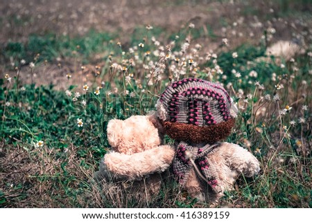 Teddy bears sitting on the beautiful grass and white flowers with love. Concept about love and relationship,selective focus - stock photo