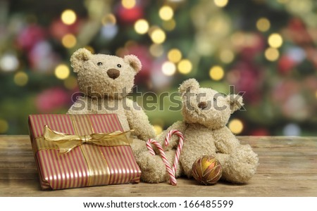 teddy bears with christmas present, christmas lights in background - stock photo