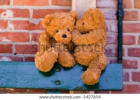 Teddy whispering in the ear - stock photo