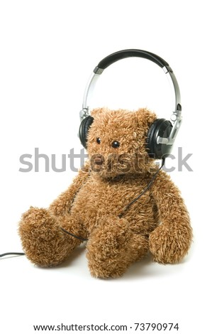 Teddybear with headphones on a white background. Concept of audiobook for children. - stock photo