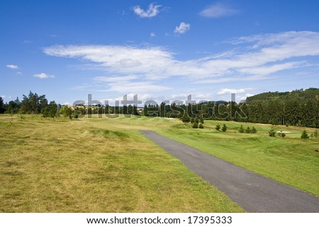 tee box and fairway of a beautiful golf course with dramatic summer sky - stock photo