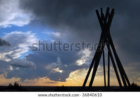 tee-pee frame in silhouette against stormy south dakota sky - stock photo