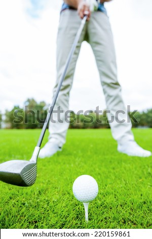 Teeing off. Close-up of golfer teeing off while standing on golf course - stock photo