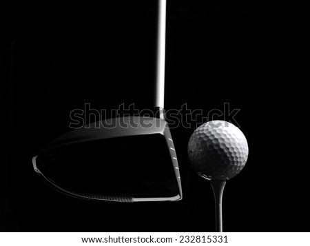 Teeing off in a game of golf with a golf ball and golf tee, isolated on black with copy space.  - stock photo