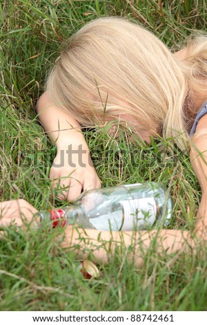 Teen alcohol addiction (drunk teen with vodka bottle) - stock photo