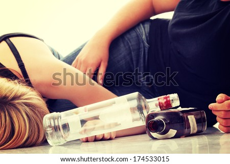 Teen alcohol addiction (drunk teens with vodka and whisky bottle) - stock photo