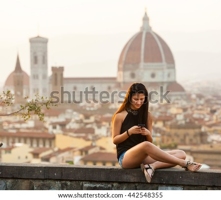Teen at sunset in Florence uses the smartphone, Cathedral of Santa Maria del Fiore on the background.