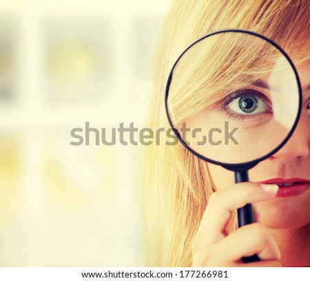 Teen blond girl with magnifier - stock photo