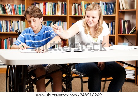 Teen boy and girl goofing around in the library.  The boy is disabled in a wheelchair.   - stock photo