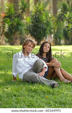 Teen boy and girl in a bright sunny summer day sitting on the grass in the park. - stock photo