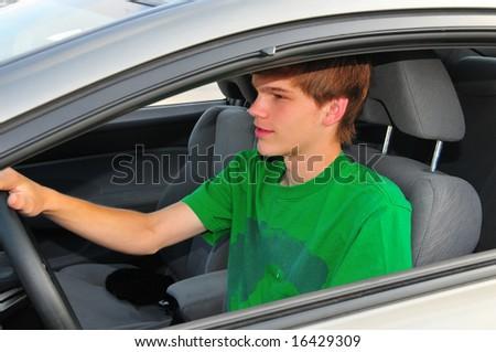 Teen boy behind the wheel of a car - stock photo
