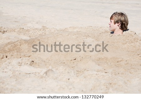 Teen boy buried in the sand - stock photo