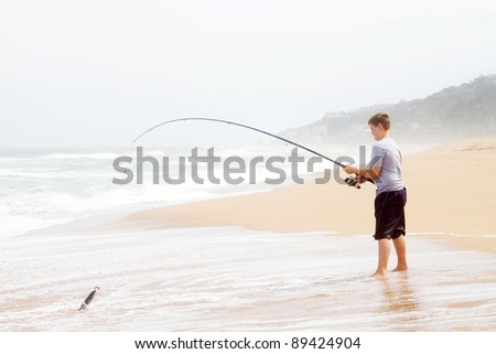 teen boy catching a fish with fishing rod on beach - stock photo