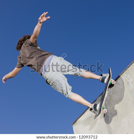 Teen boy does tricks in the half pipe at a skate park - stock photo