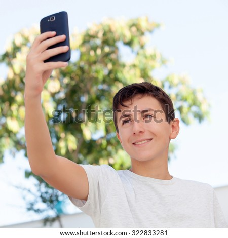 Teen boy getting a photo with the phone in the street - stock photo