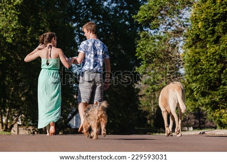 Teen Boy Girl Walking Away Teenagers girl boy hangout summers day home talk laugh playtime walking away - stock photo
