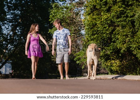 Teen Boy Girl Walking Talking Dog Teenagers girls boy hangout summers day home talk laugh playtime walking with dogs - stock photo
