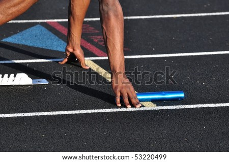 Teen Boy in the Starting Blocks for a Relay Race - stock photo