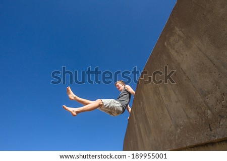 Teen Boy Jumping Blue Sky Teen boy jumping off wall against blue sky onto beach