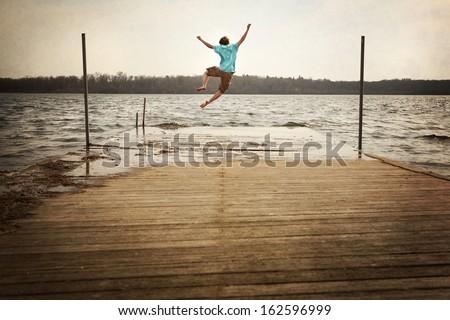 Teen Boy Jumping off a dock - stock photo