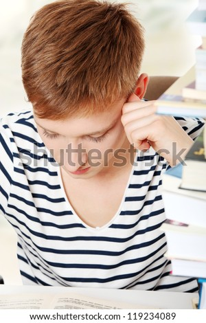 Teen boy learning at the desk - stock photo
