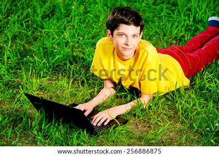 Teen boy lying with his laptop on grass at a park. Summer day.  - stock photo