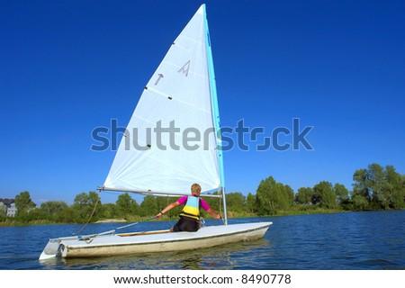 Teen boy navigates his yacht on river. Shot in July, Dnieper river, Ukraine. - stock photo